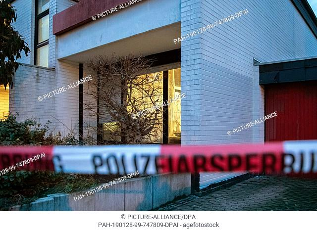 28 January 2019, Lower Saxony, Lehrte: A police barrier tape hangs in front of a house, while a forensic officer works in an apartment