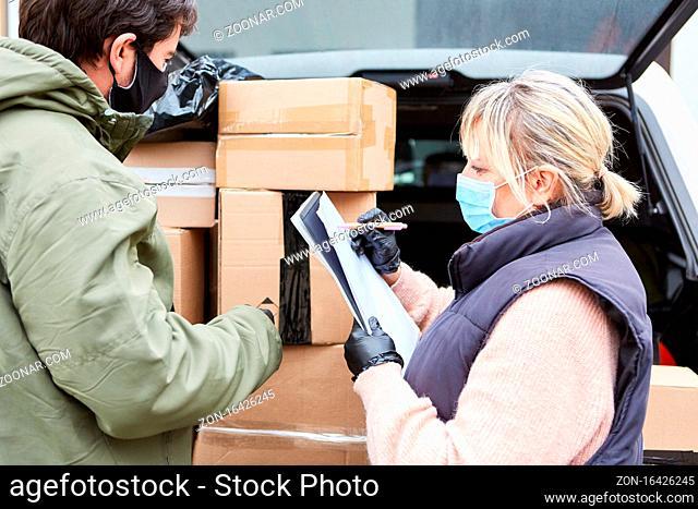 Paketdienst Team prüft Lieferungen vor offenem Laderaum mit vielen Paketen
