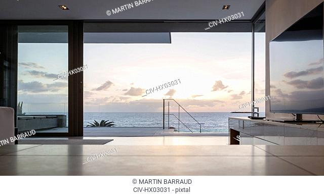 Home showcase living room and patio with tranquil sunset ocean view