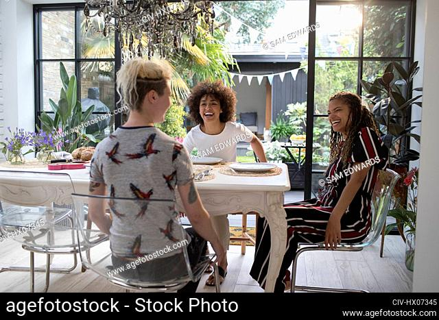 Happy young women friends at sunny dining room table