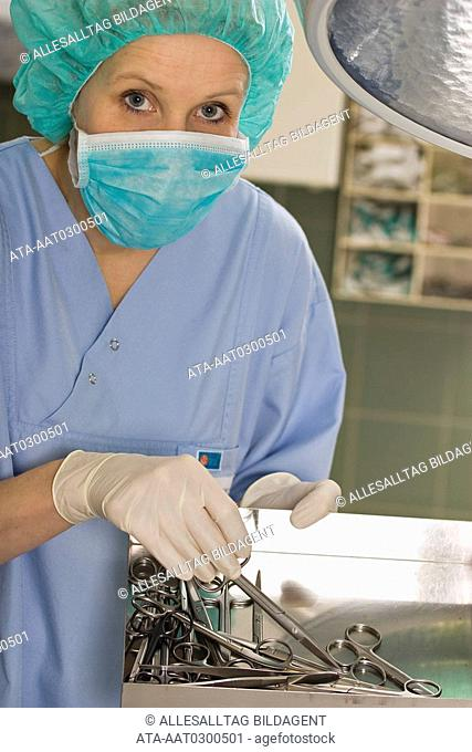 Surgery nurse with set of instruments