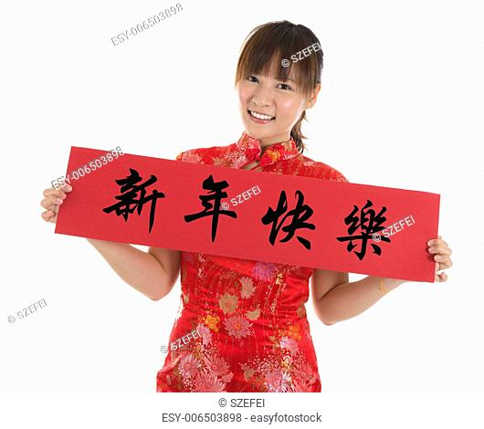 Asian woman with Chinese traditional dress cheongsam or qipao holding couplet, the Chinese word means Happy New Year. Female model isolated on white background