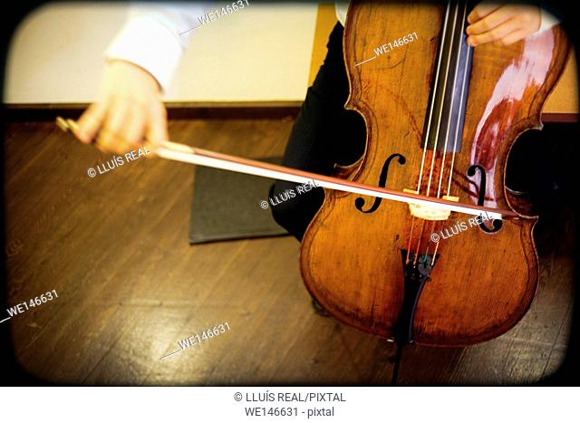 Close-up of a unrecognizable cellist rehearsing in a theater