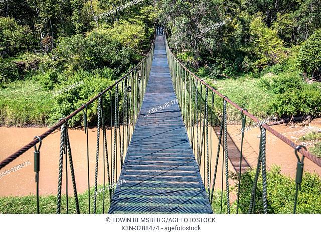 A pederstian bridge crossing a murky river in Maasai Mara National Reserve, Kenya