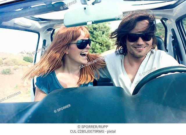Young couple in off road car