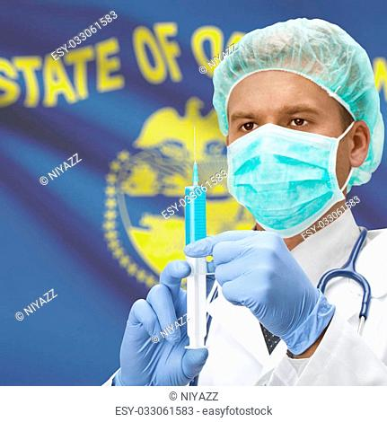 Doctor with syringe in hands and USA states flags on background - Oregon