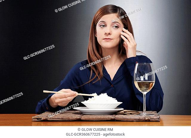 Woman talking on a mobile phone and eating rice