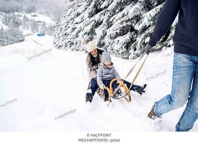Happy family with sledge in winter landscape