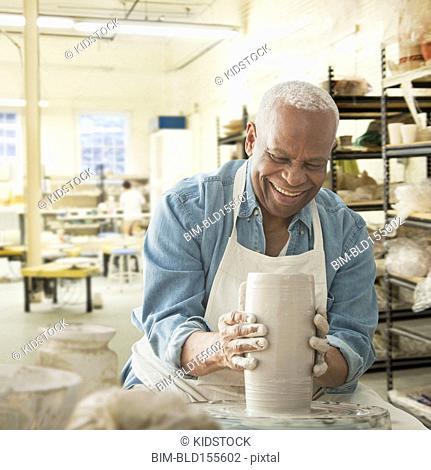 Older black man forming pottery on wheel in studio