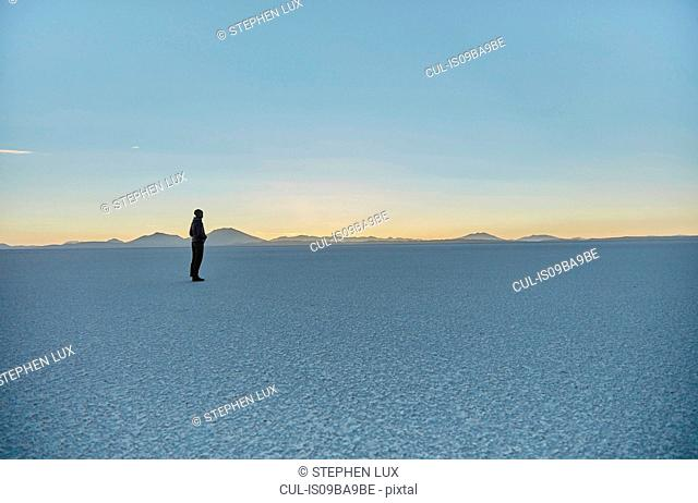 Woman standing on salt flats, looking at view, Salar de Uyuni, Uyuni, Oruro, Bolivia, South America