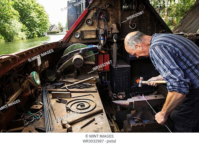 Blacksmith working in a small space on his narrowboat, a barge on river, bending over the anvil and shaping hot metal