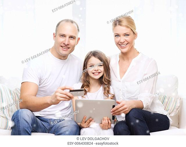 family, holidays, shopping, technology and people concept - happy family with tablet pc computer and credit card over snowflakes background