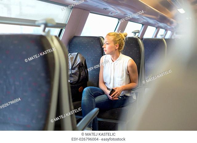 Young woman looking trough window while traveling by train