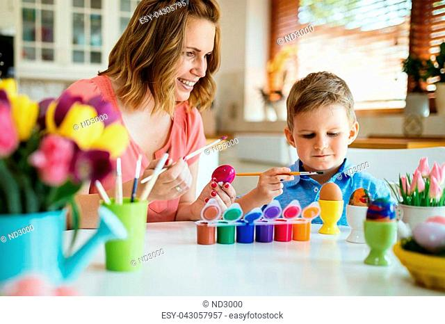 Mother and son are painting eggs. Happy family are preparing for Easter
