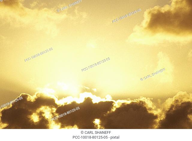 Bright sun shining behind the clouds in yellow sunset sky