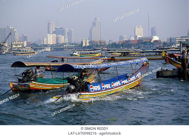 Chao Phraya River. Tall modern buildings, hotels. Traditional longtail boat. River traffic