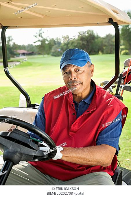 Black man driving golf cart