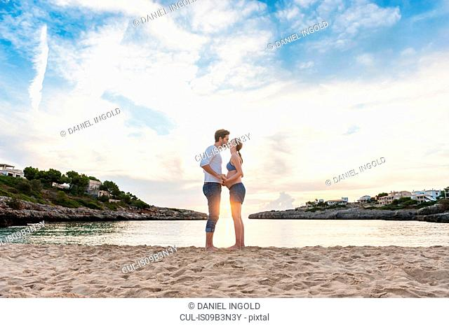 Pregnant woman and man standing face to face on beach, kissing