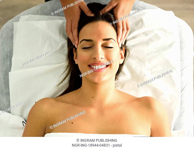 Top view of young caucasian smiling woman receiving a head massage in a spa center with eyes closed. Female patient is receiving treatment by professional...