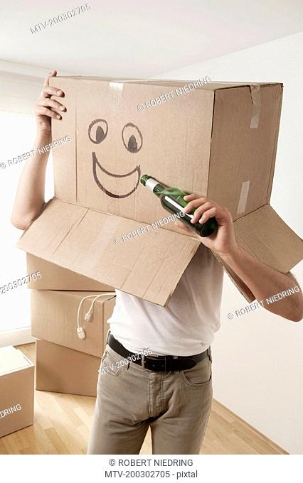 Man wearing happy face moving box over head and pretending to drink beer, Bavaria, Germany