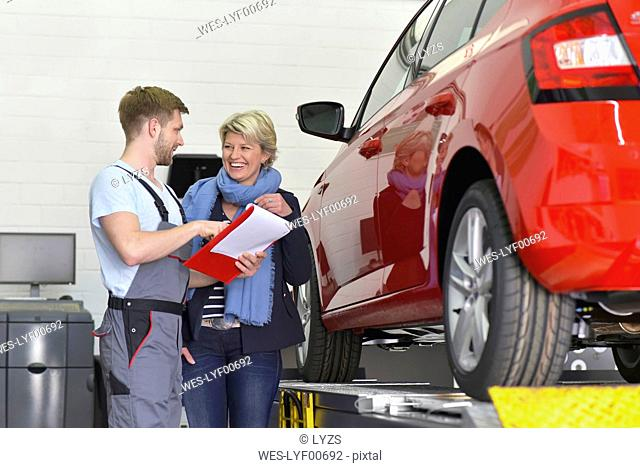Car mechanic with client in workshop at car
