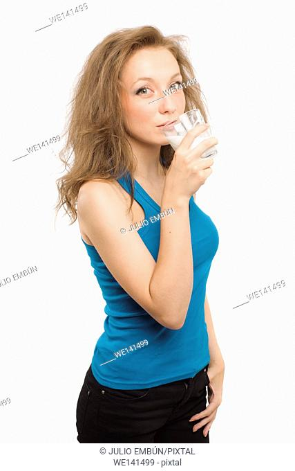 Caucasian young girl drinks milk from a glass