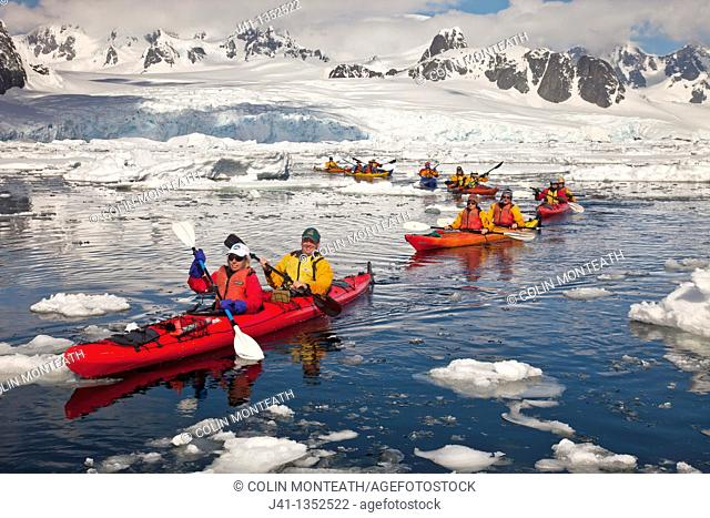 Kayakers paddling in brash ice, entrance to Lemaire Channel, near Petermann Island, Antarctic Peninsula