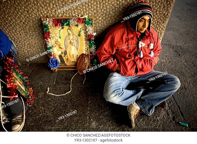 A pilgrim sits by an image of Our Lady of Guadalupe virgin in Mexico City, December 6, 2008  Hundreds of thousands of Mexican pilgrims converged on the Our Lady...