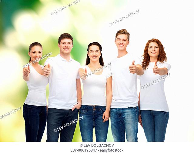advertising, ecology, nature, friendship and people concept - group of smiling teenagers in white blank t-shirts showing thumbs up over green background