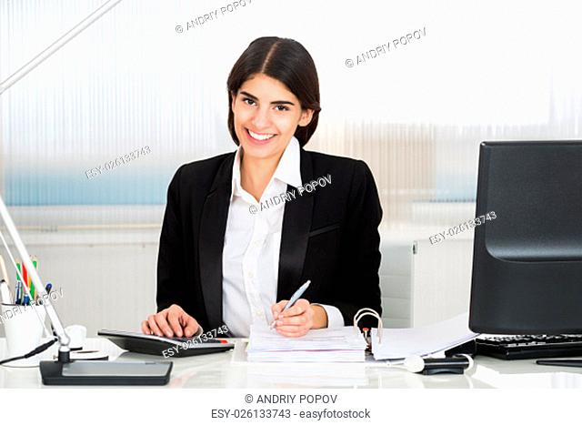 Young female accountant calculating finance with calculator at desk in office