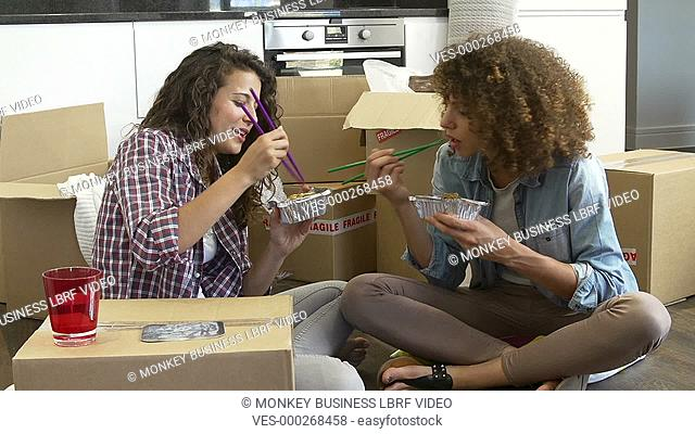Two women celebrating moving into new home with takeaway chinese meal.Shot on Sony FS700 in PAL format at a frame rate of 25fps
