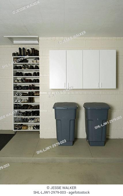 GARAGE STORAGE: Clean storage shelves and cabinets, two garbage cans under close cabinet, shoe rack on left