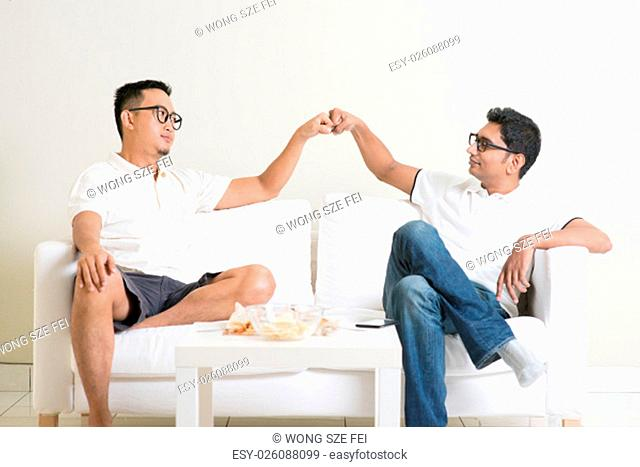 Man sitting on sofa and giving fist bump to friend at home. Multiracial people friendship