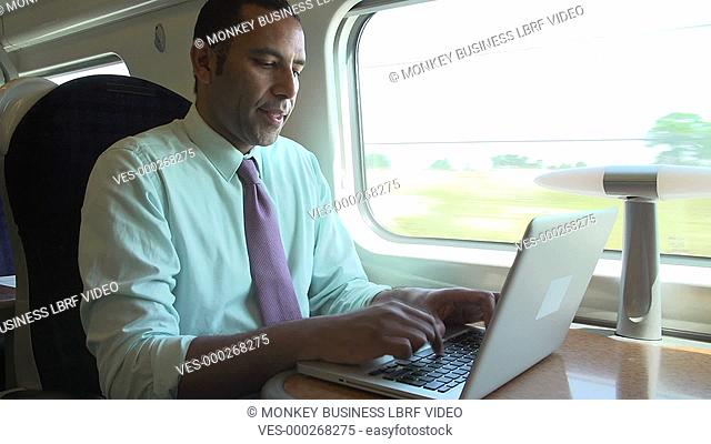 Businessman sitting at table working at laptop.Shot on Sony FS700 in PAL format at a frame rate of 25fps