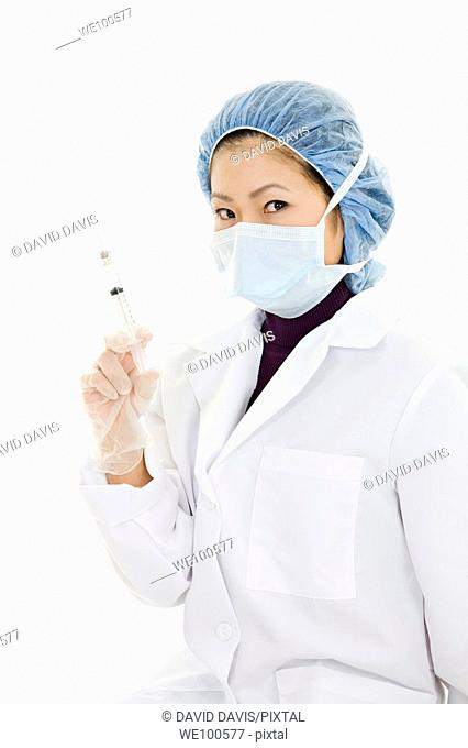 Female doctor holding a syringe on white background