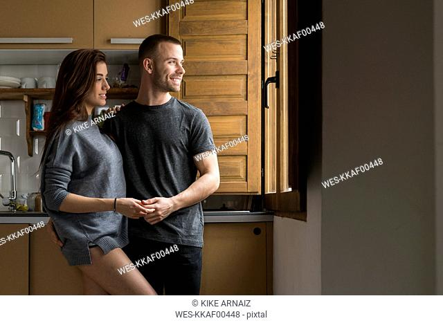 Amorous couple standing in kitchen, holding hands