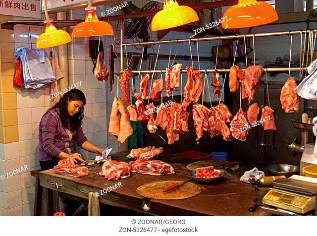 Verkäuferin an einem Fleischstand auf dem Markt von Sai Kung Stadt, Hongkong / At the butcher's on the meat market of Sai Kung town, Hong Kong