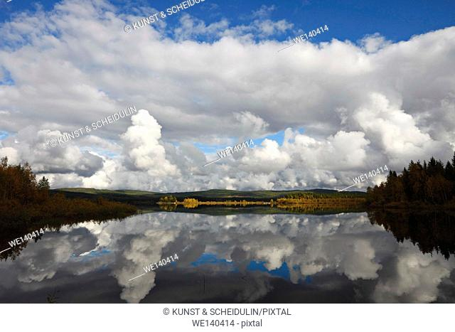 Cumulus clouds are towering over a lake in autumn. The forest on the shore is reflected in the still water