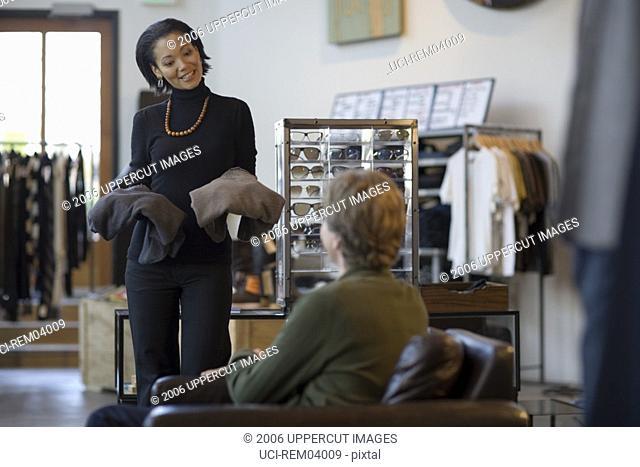 Saleswoman showing man clothing