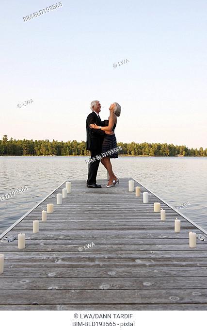 Senior Caucasian couple dancing on pier