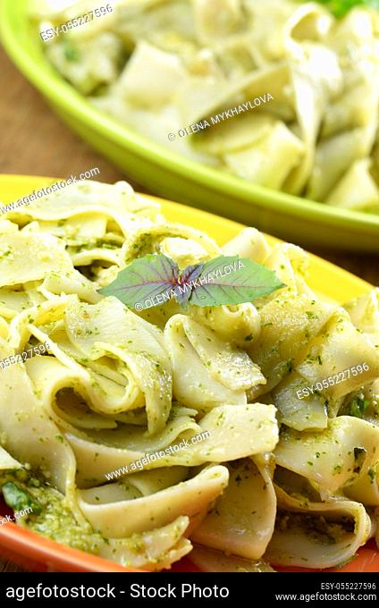 Pasta tagliatelle with pesto sauce and basil