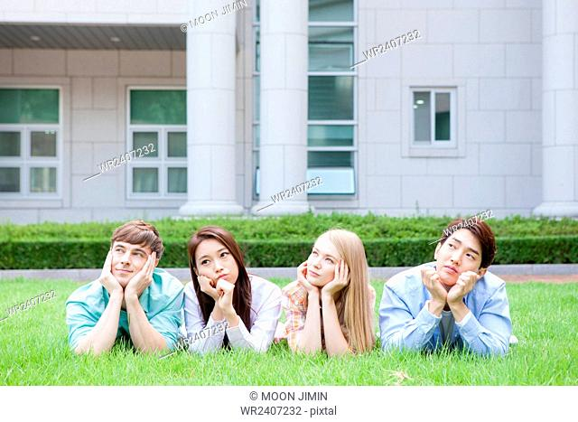 Domestic students and international students in college lying on their front on a grass and staring up with a smile outside on campus