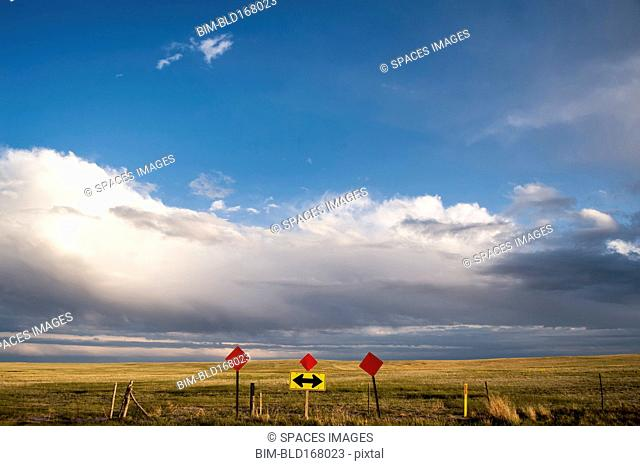 Traffic sign in remote field under clouds
