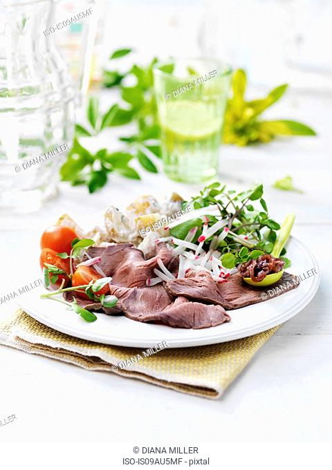 Plate of natural salad, with roast beef, tomato and potatoes on garden table
