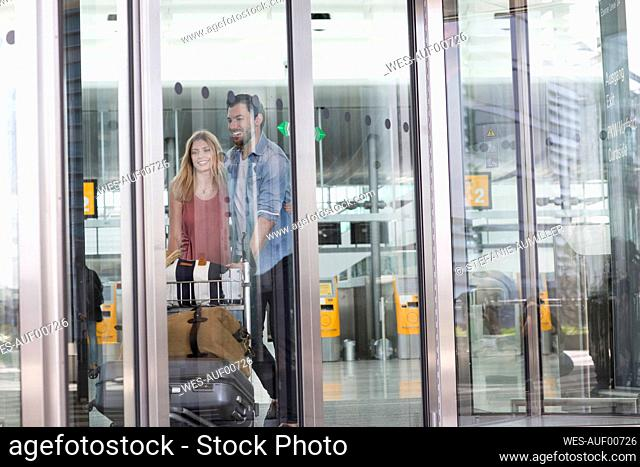 Young couple with luggage trolley at airport terminal