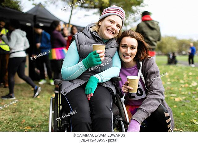 Portrait smiling woman in wheelchair with friend, drinking water at charity race in park