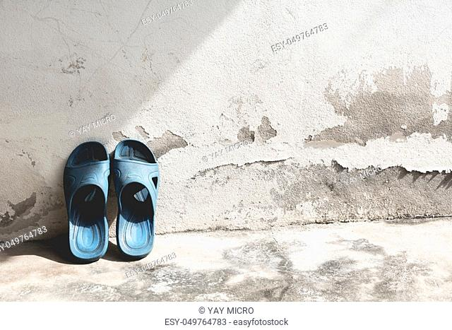Blue flip flops on the old concrete wall background