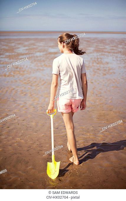 Teenage girl dragging shovel in wet sand on sunny summer beach