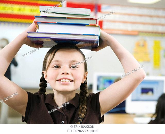 Elementary student holding a stack of books on her head