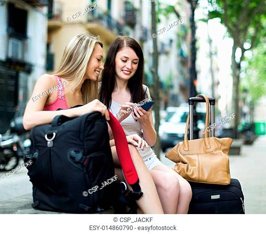Two female friends with luggage using the map